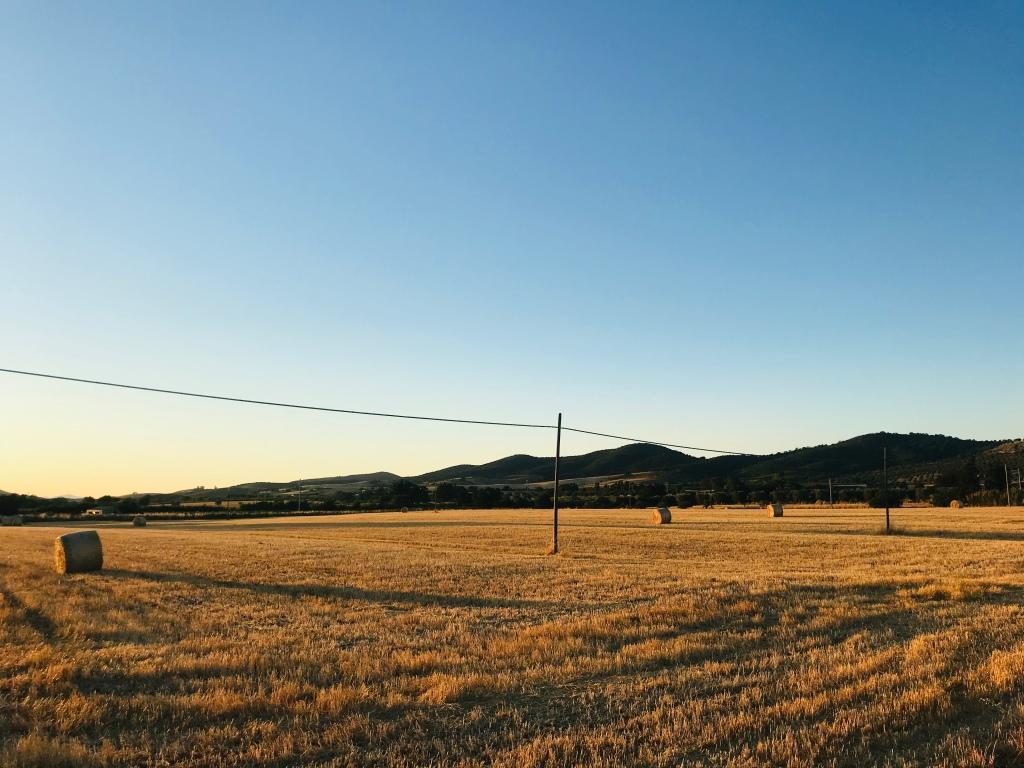 Campi con balle di fieno al tramonto - Maremma, Toscana, Italia