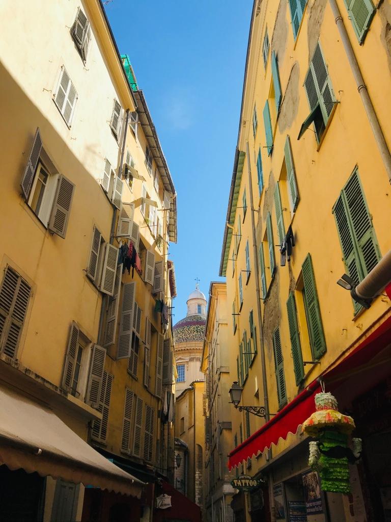 Una viuzza di Nizza Vecchia e, sullo sfondo, la cupola della la Cathédrale Sainte-Réparate de Nice - Nizza, Costa Azzurra, Francia